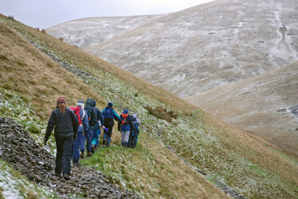 A group of hikers walking along a path in the English Pennines with slightly snow-covered mountains in the background